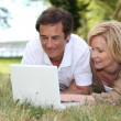 Royalty-Free Stock Photo: Couple looking at their laptop in a park