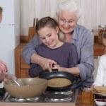 Family cooking pancakes — Stock Photo