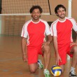 Royalty-Free Stock Photo: Two volleyball players kneeling with ball on indoor court