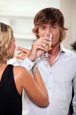 Young couple drinking champagne with their arms entwined — Stock Photo