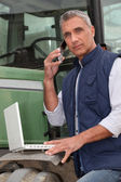 Farmer with a laptop and cellphone — Stock Photo