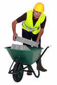 Mason carrying bricks in wheel barrow — Stock Photo