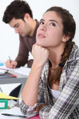 Young woman daydreaming in class — Stock Photo