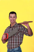A carpenter carrying a plank and a handsaw. — Stock Photo