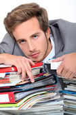 Young man lying down on a desk full of binders and notebooks — Stock Photo