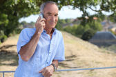 Grey-haired man making telephone call in park — Stock Photo