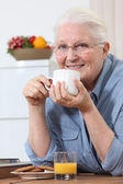 Elderly lady enjoying cup of tea — Stock Photo