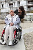 Young woman pushing an elderly woman in a wheelchair — Stock Photo