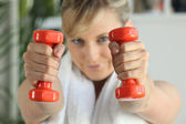 Woman lifting weights in the gym — Stock Photo