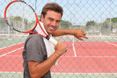 Man stood in front of tennis court holding racket over shoulder — Stock Photo