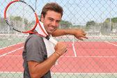 男子站在网球场举行球拍在肩膀上 — 图库照片