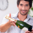 A man offering a bottle of champagne. — Stock Photo