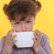 Little girl drinking from bowl - Stock Photo