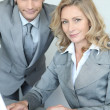 A businessman and a businesswoman working in front of a laptop and looking — Stock Photo #8080481