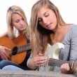 Two young women playing the guitar. — Stock Photo