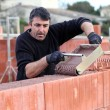 Man pouring wet cement on to wall — Stock Photo