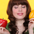 Woman with eyes closed holding peppers — Stock Photo