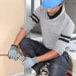 Stock Photo: Electrician fixing wall electrics
