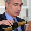 A mature man pouring champagne. — Stock Photo #8081439