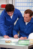 Blue collars in office: apprentice and instructor — Stock Photo