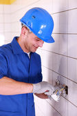 Man wiring a power socket in a tiled room — Stock Photo