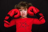 Niña con guantes de boxeo tirando una cara contra el fondo negro — Foto de Stock