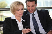 Businessman and woman looking at phone — Stock Photo