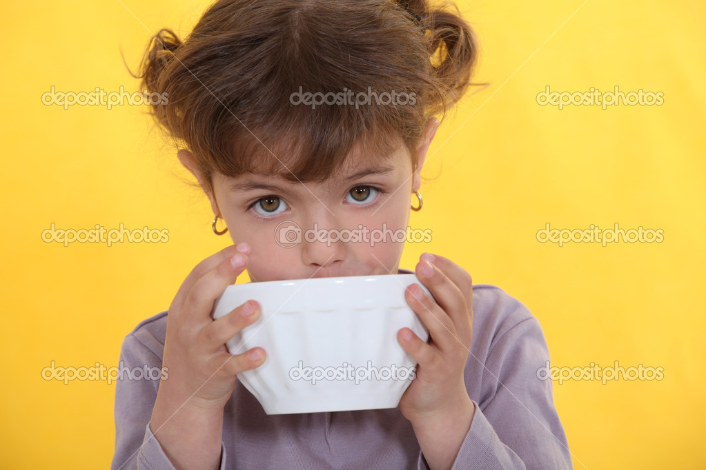 Little girl drinking from bowl — Stock Photo #8080214