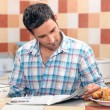 Man reading his newspaper at the breakfast table — Stock Photo