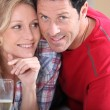 Blond woman holding champagne laid next to husband — Stock Photo