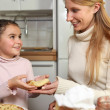 Stock Photo: Little girl giving her mother crepe