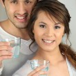 Enthusiastic man and woman with glasses of water - Stock Photo