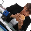 Woman eating burger at desk — Stock Photo
