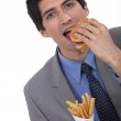 Businessman eating burger and fries — Stock Photo