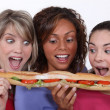 A group of friends eating a long sandwich — Stock Photo #8101483