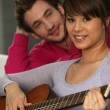 A man looking a woman playing guitar — Stock Photo