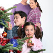 Family gathered around Christmas tree — Stock Photo