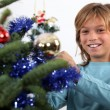 Smiling teenage boy decorating Christmas tree — Stock Photo