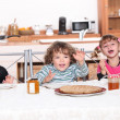 Three children gathered around breakfast table — Stock Photo