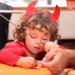 A little kid dressed as the devil drawing. — Stock Photo