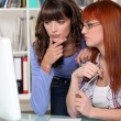 Two confused girls looking at computer screen — Foto de Stock