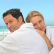 Couple on the dunes in towelling robes — Stock Photo