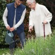 Young man watering plants with older woman — Stock Photo #8102215