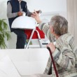 Young man putting up a light for an elderly woman — Stockfoto