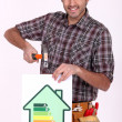 Craftsman nailing an energy consumption label — Stock Photo #8102323