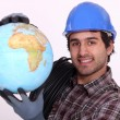 Manual worker holding globe - Stock Photo