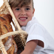 A little girl hugging a wickerwork bread bin full of bread - Stock Photo
