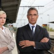 A blonde woman and a mature man well dressed in a train station — Stok fotoğraf
