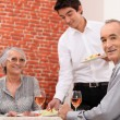 Old couple having meal in restaurant - Foto Stock