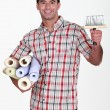 Portrait of do-it-yourselfer carrying wallpaper rolls and brush — Stock Photo #8105269